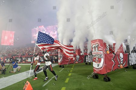 Tampa Bay Buccaneers safety Andrew Adams (26) carries the United States flag onto the field during team introductions before an NFL football game against the Dallas Cowboys, in Tampa, Fla