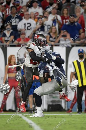 Dallas Cowboys running back Ezekiel Elliott (21) is tackled by Tampa Bay Buccaneers safety Andrew Adams (26) during the second half of an NFL football game, in Tampa, Fla