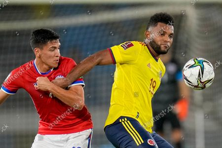Chile's Macelino Nunez, left, and Colombia's Miguel Borja fight for the ball during a qualifying soccer match for the FIFA World Cup Qatar 2022 in Barranquilla, Colombia