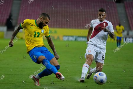 Brazil's Daniel Alves, left, kicks the ball during a qualifying soccer match against Peru for the FIFA World Cup Qatar 2022 at Pernambuco Arena in Recife, Brazil, Thursday, Sept.9, 2021