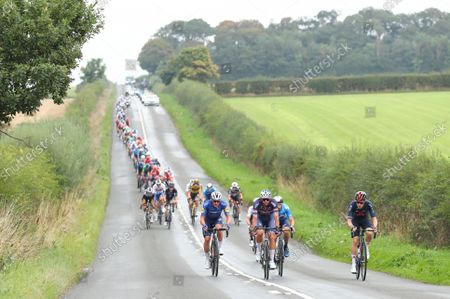 The peloton heads out of Carlisle with Deceuninck Quick-Step's Thomas Mein, INEOS Grenadiers' Rohan Dennis & Alpecin Fenix's Jimmy Janssens on the front.