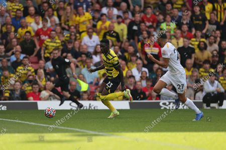 Ismaila Sarr of Watford runs with the ball chased by Romain Saiss of Wolves