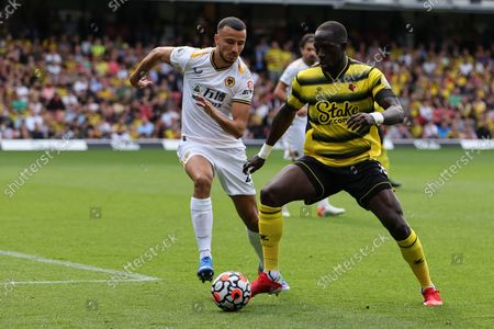 Moussa Sissoko of Watford with the ball under pressure from Romain Saiss of Wolves