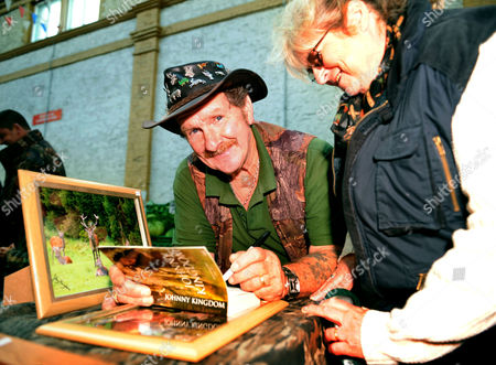 Johnny Kingdom signing copies of his book on his stall