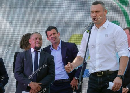 Stock Photo of Luis Figo (C), the former Portuguese  professional footballer and Real Madrid player, with Roberto Carlos (L),  former Brazilian professional footballer and ambassador of Real Madrid Foundation, listen a speech of Kiev's Mayor and former heavyweight boxing champion Vitali Klitschko (R) during the opening ceremony of the Real Madrid Foundation soccer school in the Kiev, Ukraine, 10 September 2021. Spanish LaLiga club Real Madrid CF develops its social and cultural  programmes with Real Madrid Foundation which unites more than 450 football schools in 80 countries. Real Madrid Foundation helps to promote the values inherent in sport, and its role as an educational tool both in Spain as well as abroad.