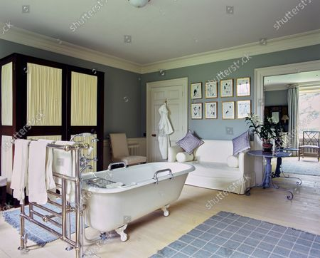 A guest bathroom at the Wormsley Estate, home of Victoria and J. Paul Getty, Jr. in England, designed by David Mlinaric, includes a group of c. 1895 Aubrey Beardsley illustrations, an Edwardian clawfoot freestanding tub, mahogany Regency cupboard, and bleached beech wood floors.