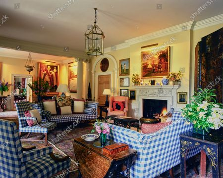 The living room in the Wormsley Estate, home of Victoria and J. Paul Getty, Jr. in England, includes a large open living room with gingham upholstered furniture and historic paintings including a portrait of Lord Hunsdon by Marcus Gheeraerts.