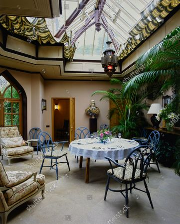 The Gothic conservatory at the Wormsley Estate, home of Victoria and J. Paul Getty, Jr. in England, designed by Johnston Cave Associates with interior design by David Mlinaric, includes a dining table and large houseplants.