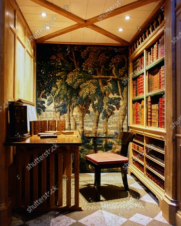 A corner of the library at Wormsley Estate, home of Victoria and J. Paul Getty, Jr. in England, includes a 17th century Brussels made tapestry, oak writing desk, and one-armed ebony chair.
