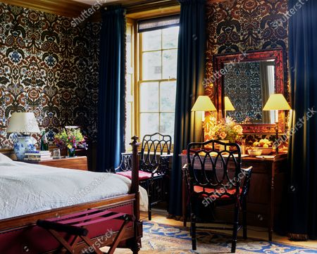 A guest bedroom at the Wormsley Estate, home of Victoria and J. Paul Getty, Jr. in England, designed by David Mlinaric with a 19th century Gillows bed and dressing table, 18th century lacquered armchairs, and a 17th century tortoiseshell framed mirror,.