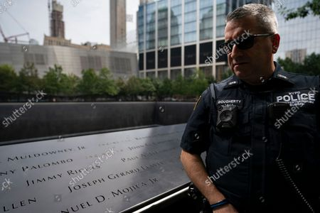 """Officer Michael Dougherty, a 25-year veteran, stands beside the south reflecting pool of the 9/11 Memorial & Museum where names of his deceased colleagues and friends are displayed, in New York. """"Tourists sometimes ask, 'What is this area?',"""" Dougherty said. """"I don't take offense to it. I like explaining to them where the buildings stood, what this is all about, just to keep the memory of everyone here alive"""