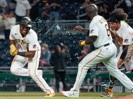 Pittsburgh Pirates' Ke'Bryan Hayes, left runs from teammates Cole Tucker, right, and Mitch Keller, left, and Anthony Alford, center, after driving in Ben Gamel with the winning run in the ninth inning of a baseball game against the Washington Nationals, in Pittsburgh. The Pirates won 4-3