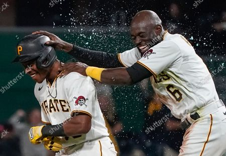 Pittsburgh Pirates' Ke'Bryan Hayes, left, celebrates with Anthony Alford after driving in the winning run in the team's baseball game against the Washington Nationals, in Pittsburgh. The Pirates won 4-3