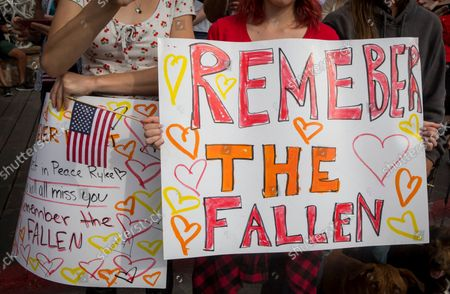 Jenna Christie, 17, and Emma Stone, 17, friends of Marine Lance Cpl. Rylee McCollum, show their support during his procession in Jackson, Wyo., on . McCollum was one of the service members killed in Afghanistan after a suicide bomber attacked Hamid Karzai International Airport on Aug. 26