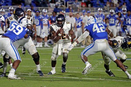 North Carolina A&T quarterback Kingsley Ifedi (12) runs against Duke defensive end Michael Reese (59) and linebacker Shaka Heyward (42) during the second half of an NCAA college football game in Durham, N.C