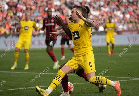 Leverkusen's Odilon Kossounou fouls Dortmund's Marco Reus followed by a decisive penalty during the German Bundesliga soccer match between Bayer Leverkusen and Borussia Dortmund in Leverkusen, Germany