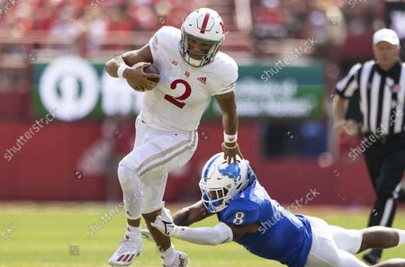 Nebraska quarterback Adrian Martinez (2) carries the ball against Buffalo's James Patterson (8) during the first half of an NCAA college football game, at Memorial Stadium in Lincoln, Neb