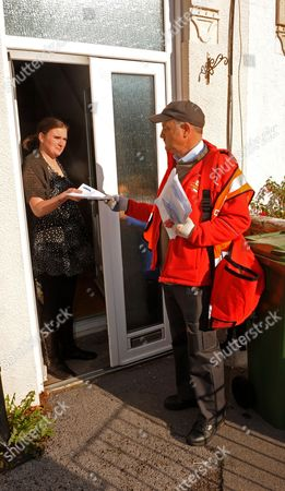 Postman Andrew Goater delivering the mail by hand to Carol White