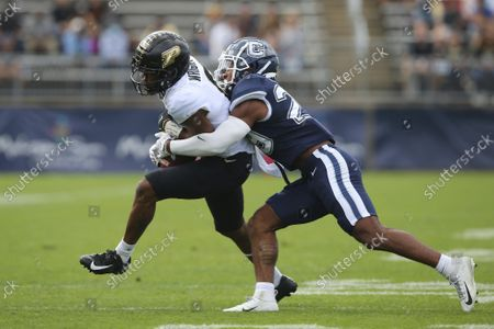 Stock Image of Purdue wide receiver Milton Wright (0) is tackled by Connecticut linebacker Jordan Morrison (29) during an NCAA football game, in East Hartford, Conn