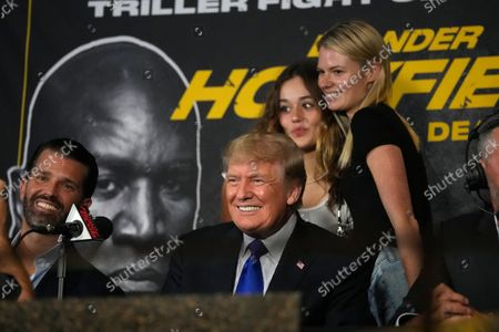 Stock Picture of Former President Donald Trump, center, smiles for a picture with supporters as he and son Donald Trump Jr., left, prepare to provide commentary for a boxing event headlined by a bout between former heavyweight champ Evander Holyfield and former MMA star Vitor Belfort, in Hollywood, Fla