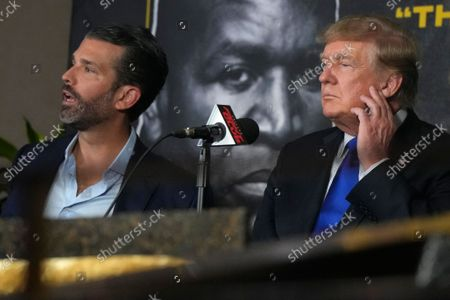Former President Donald Trump, right, and son Donald Trump Jr. prepare to provide commentary for a boxing event headlined by a bout between former heavyweight champ Evander Holyfield and former MMA star Vitor Belfort, in Hollywood, Fla