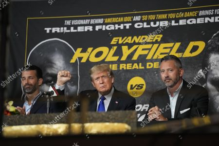 Stock Photo of Former President Donald Trump, center, salutes cheering fans and he and son Donald Trump Jr., left, prepare to provide commentary for a boxing event headlined by a bout between former heavyweight champ Evander Holyfield and former MMA star Vitor Belfort, in Hollywood, Fla