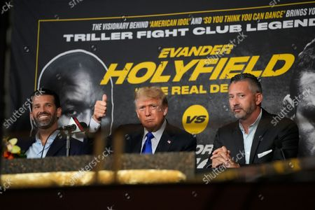 Former President Donald Trump, center, gives a thumbs-up to cheering supporters as he and his son Donald Trump Jr., left, prepare to provide commentary for a boxing event headlined by a bout between former heavyweight champ Evander Holyfield and former MMA star Vitor Belfort, in Hollywood, Fla