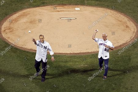 Former New York Yankees manager Joe Torre, left, and former New York Mets manager Bobby Valentine throw out ceremonial first pitches before a baseball game, in New York