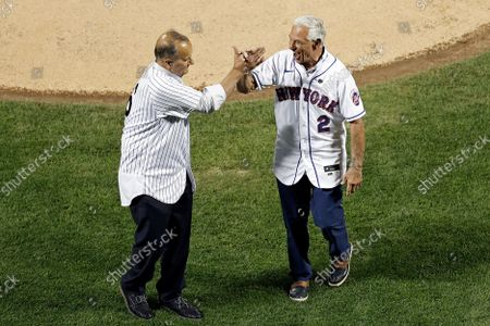 Former New York Yankees manager Joe Torre, left, and former New York Mets manager Bobby Valentine throw out the ceremonial first pitch's before a baseball game, in New York