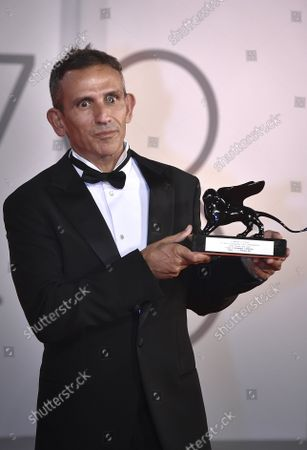 """Director Michelangelo Frammartino poses with the Special Jury Prize for """"Il Buco"""" (The Hole) at the awards winner photocall during the 78th Venice International Film Festival on Saturday, September 11, 2021 in Venice, Italy."""