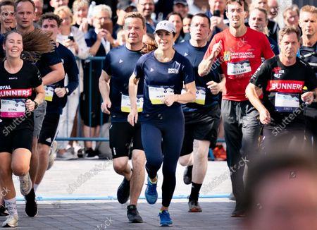 Stock Image of Crown Princess Mary of Denmark (C) arrives in the finish area as she runs 5 km during the Royal Run in Aalborg, Denmark, 12 September 2021.