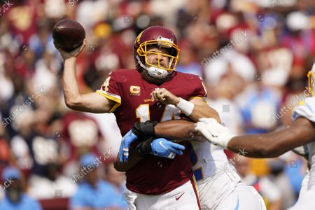 Washington Football Team quarterback Ryan Fitzpatrick (14) is tackled by Los Angeles Chargers linebacker Uchenna Nwosu (42) during the first half of an NFL football game, in Landover, Md. Fitzpatrick was injured on this play and replaced by Washington Football Team quarterback Taylor Heinicke (4
