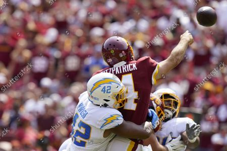 Washington Football Team quarterback Ryan Fitzpatrick (14) is hit from behind by Los Angeles Chargers linebacker Uchenna Nwosu (42), while throwing the ball during the first half of an NFL football game, in Landover, Md. Fitzpatrick was injured on the play and replaced by Washington quarterback Taylor Heinicke