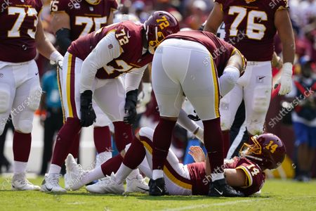 Members of the Washington Football Team check on condition of teammate quarterback Ryan Fitzpatrick (14) who lays on the field after being injured on a hit by Los Angeles Chargers linebacker Uchenna Nwosu during the first half of an NFL football game, in Landover, Md