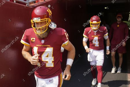Washington Football Team quarterbacks Ryan Fitzpatrick (14) and Taylor Heinicke (4) take the field for warmups prior to the start of the first half of an NFL football game against the Los Angeles Chargers, in Landover, Md