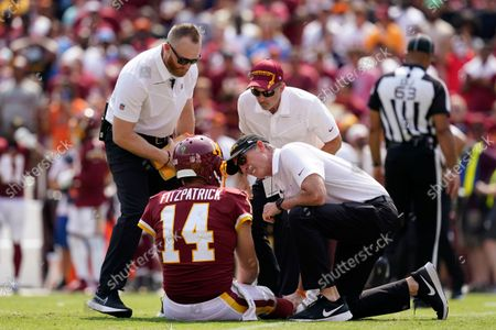 Members of the Washington Football Team staff check on condition of quarterback Ryan Fitzpatrick (14) after he was injured on a hit by Los Angeles Chargers linebacker Uchenna Nwosu during the first half of an NFL football game, in Landover, Md
