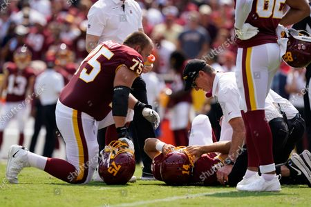 Members of the Washington Football Team check on condition of quarterback Ryan Fitzpatrick (14) after he was injured on a hit by Los Angeles Chargers linebacker Uchenna Nwosu during the first half of an NFL football game, in Landover, Md
