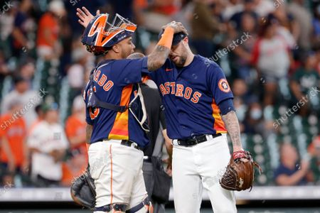 Houston Astros catcher Martin Maldonado, left, and closing pitcher Ryan Pressly, right, pat each other on the head after their 3-1 win over the Los Angeles Angels after a baseball game, in Houston