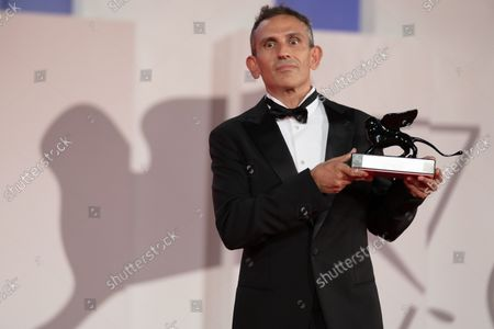 """Stock Picture of Director Michelangelo Frammartino poses with the Special Jury Prize for """"Il Buco"""" (The Hole) at the awards winner photocall during the 78th Venice International Film Festival on September 11, 2021 in Venice, Italy."""