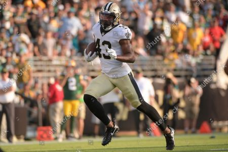 New Orleans Saints free safety Marcus Williams runs after intercepting a pass against the Green Bay Packers during the second half of an NFL football game, in Jacksonville, Fla