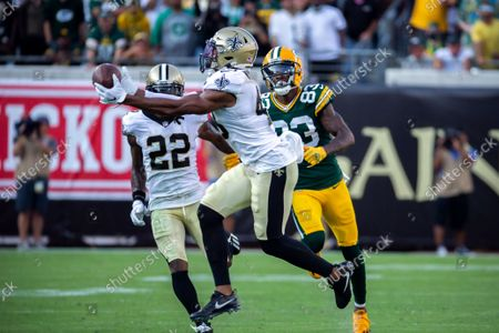 New Orleans Saints free safety Marcus Williams, left, intercepts a pass in front of Green Bay Packers wide receiver Marquez Valdes-Scantling (83) during the second half of an NFL football game, in Jacksonville, Fla