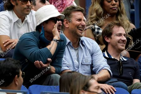 Brad Pitt, left, Bradley Cooper, center and Joseph Mazzello react as they watch play between Novak Djokovic, of Serbia, and Daniil Medvedev, of Russia, during the men's singles final of the US Open tennis championships, in New York