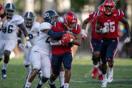 Stock Image of Running back Larry McCammon (3) runs with ball and is tackled by Georgia Southern cornerback Seth Robertson (20) during an NCAA football game on in Boca Raton, Fla