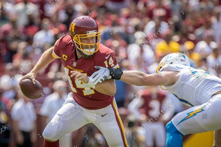 Washington Football Team quarterback Ryan Fitzpatrick (14) evades the rush of Los Angeles Chargers defensive end Joey Bosa (97) during the NFL regular season game between the Los Angeles Chargers and the Washington Football Team at FedEx Field in Landover, Maryland Photographer: Cory Royster