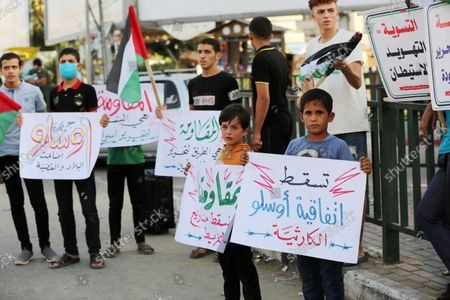 Palestinians hold placadrs during a rally on the occasion of the 28th anniversary of the Oslo accords between Palestinians and Israel, in Gaza city on September 13, 2021. In 1993, Israeli Prime Minister Yitzhak Rabin and PLO chairman Yasser Arafat signed the Oslo Accords.
