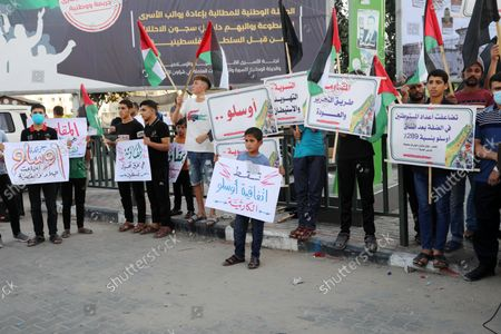 Stock Image of Palestinians hold placadrs during a rally on the occasion of the 28th anniversary of the Oslo accords between Palestinians and Israel, in Gaza city on September 13, 2021. In 1993, Israeli Prime Minister Yitzhak Rabin and PLO chairman Yasser Arafat signed the Oslo Accords.