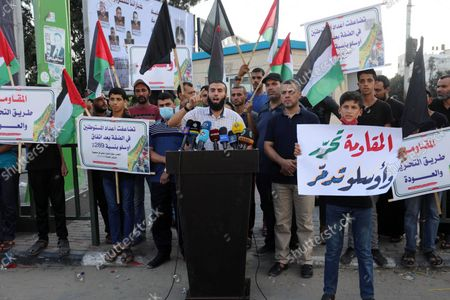 Stock Photo of Palestinians hold placadrs during a rally on the occasion of the 28th anniversary of the Oslo accords between Palestinians and Israel, in Gaza city on September 13, 2021. In 1993, Israeli Prime Minister Yitzhak Rabin and PLO chairman Yasser Arafat signed the Oslo Accords.