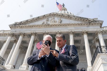 Rep. Mike Thompson, D-Calif., left, shows Sen. Joe Manchin, D-W.Va., right, something on his phone following a Congressional Remembrance Ceremony marking the 20th anniversary of the Sept. 11, 2001, terrorist attacks, on Capitol Hill in Washington