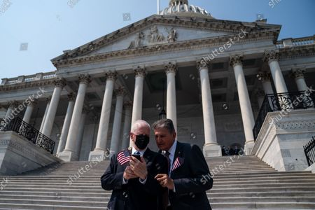 Rep. Mike Thompson (D-CA), left, speaks with Sen. Joe Manchin (D-WV), right, following a remembrance ceremony marking the 20th anniversary of the 9/11 terror attacks, held on the steps of the U.S. Capitol building on Monday, Sept. 13, 2021 in Washington, DC. After a month long recess, the Senate returns to session this week. (Kent Nishimura / Los Angeles Times)