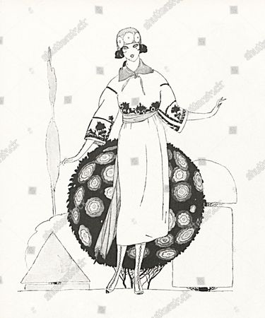 Model wearing a wide sleeved gabardine dress embroidered with Arabic motifs, belted with a crepe sash, by Poiret, paired with high lace up boots and a cloche hat, posing in front of topiary foliage.